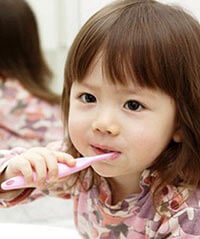 child brushing teeth with fluoride-free toothpaste