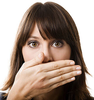 A girl covering her mouth because of halitosis